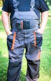 Landbouwer in donkere het werkoverall met steunen stock fotografie