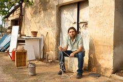 Landbouwer in een Buitenhuis Stock Fotografie