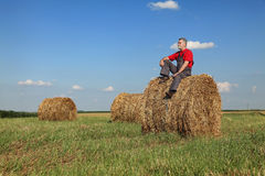 Landbouwer en baal van hooi op gebied stock fotografie