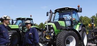 Landbouwer en werktuigkundige met grote tractoren stock afbeelding