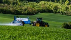 Landbouwer het bespuiten met tractor op het tarwegebied Stock Foto