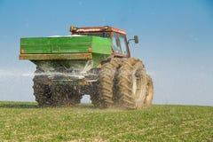 Landbouwer het bevruchten tarwe met stikstof, fosfor, kaliummeststof stock foto