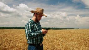 Landbouwer het texting op smartphone stock footage