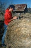 Landbouwer met laptop computer op hooibaal stock afbeeldingen