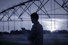 Landbouwer met tablet voor irrigatiesysteem Stock Foto's