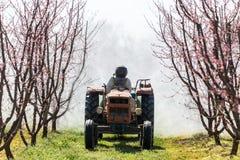 Landbouwer met tractor die een spuitbus van de luchtontploffing gebruiken royalty-vrije stock afbeeldingen