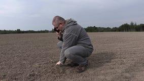 Landbouwer op de gebiedscontrole de grond en het spreken van smartphone stock video