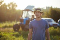 Landbouwer op het gebied met de tractor op de achtergrond bij organisch landbouwbedrijf Stock Foto