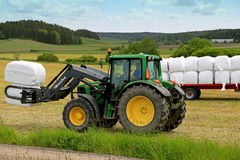 Landbouwer Stacks op Kuilvoeder met Front Loader John Deere 6330 Tracto stock foto