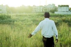 Landbouwer of zakenman wat betreft gras Stock Fotografie
