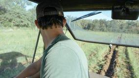 Landbouwers drijftractor op het aardappelgebied in aardappel het oogsten procédé Stock Afbeeldingen