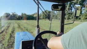 Landbouwers drijftractor op het aardappelgebied in aardappel het oogsten procédé Stock Fotografie
