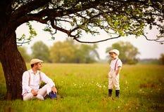 Landbouwersfamilie die pret onder een oude boom, de lenteplatteland hebben Stock Fotografie