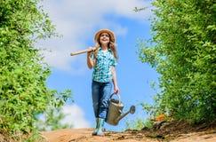 landbouwersmeisje tuinhulpmiddelen, schop en gieter zonnige openlucht van de jong geitjearbeider Familie het plakken de kant van  stock afbeeldingen