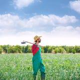 Landbouwersmens die met schoffel zijn gebied bekijken stock fotografie