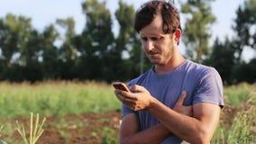 Landbouwersmens die op mobiele telefoon bij gebied van organisch ecolandbouwbedrijf spreken stock footage