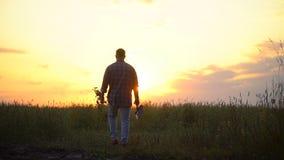 Landbouwersmens die over het gebied bij zonsondergang of zonsopgang lopen Draag een een boomzaailing en schop, Concept - werk in  stock video
