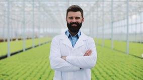 Landbouwingenieur in serre die witte laag dragen die de camera onderzoeken Portret van een glimlachende serrearbeider stock videobeelden