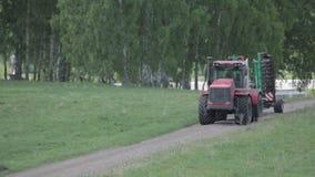 Landbouwmachine uitgespreide meststof op gecultiveerde gebiedsgrond in de zomer Het planten van gewassen stock videobeelden