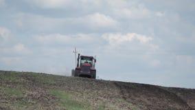 Landbouwmachine uitgespreide meststof op gecultiveerde gebiedsgrond in de zomer Het planten van gewassen Blauwe hemel stock videobeelden
