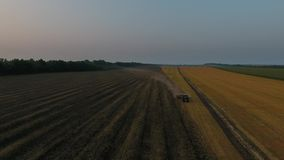 Landbouwmachines het ploegen gebiedszonsondergang stock footage