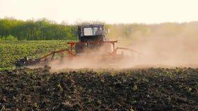 Landbouwtrekker die en gebied zaaien cultiveren Tractor met een ploegaanhangwagen die het gebied na zonsondergang ploegen stock videobeelden