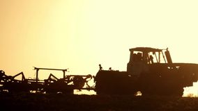 Landbouwtrekker die en gebied zaaien cultiveren Tractor met een ploegaanhangwagen die het gebied na zonsondergang ploegen stock footage