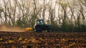 Landbouwtrekker die en gebied zaaien cultiveren Tractor met een ploegaanhangwagen die het gebied na zonsondergang ploegen stock video