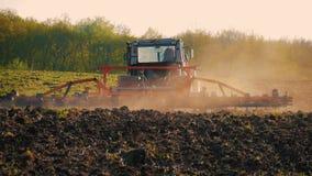 Landbouwtrekker die en gebied zaaien cultiveren Tractor die op het gebied bij zonsondergang werken stock videobeelden