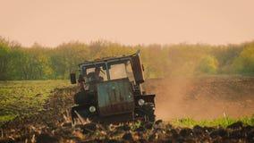 Landbouwtrekker die en gebied zaaien cultiveren Tractor die op het gebied bij zonsondergang werken stock footage