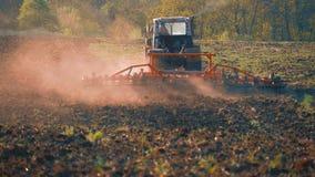Landbouwtrekker die en gebied in zonsondergang zaaien cultiveren Tractor die land voor het zaaien voorbereiden stock videobeelden