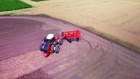 Landbouwtrekker met aanhangwagen voor ploegen die aan gecultiveerd gebied werken stock videobeelden
