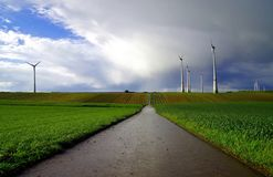 Landcape of Wind turbines in green grain fields against stormy sky stock photography