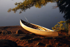 Landed Canoe. A canoe up on the shore at a camp site royalty free stock photo