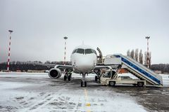 Landed white passenger airplane with attached ladder in winter airport stock photography