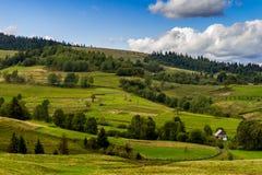 Landelijk huis dichtbij de landbouwgrond in Karpatische Mountai Stock Afbeelding