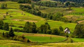 Landelijk huis dichtbij de landbouwgrond in Karpatische Mountai Royalty-vrije Stock Foto