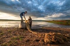 Landelijk landschap twee vissers, vader en zoon, verzamelt een zegen voor visserij in fishboat in yakutian dorp, Yakutia, Rusland stock fotografie