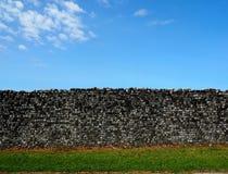 Landelijke achtergrond, Oude middeleeuwse muur met gras en blauwe hemel Royalty-vrije Stock Fotografie