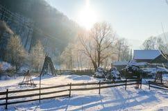 Landelijke de wintermening van een Roemeens Dorp naast het hout met een houten omheining en heel wat sneeuw Stock Foto's