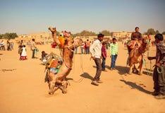 Landelijke landschap en dorpsbewoners die met kamelen dieren berijden Stock Afbeeldingen