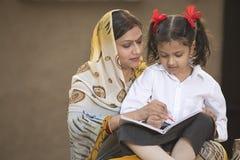 Landelijke moeder die dochter met haar thuiswerk helpen royalty-vrije stock afbeeldingen