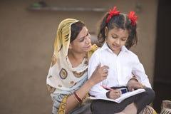Landelijke moeder die dochter met haar thuiswerk helpen stock afbeeldingen