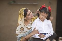 Landelijke moeder die dochter met haar thuiswerk helpen stock foto