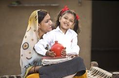 Landelijke moeder met het geld van de dochterbesparing in spaarvarken voor toekomstig onderwijs royalty-vrije stock fotografie