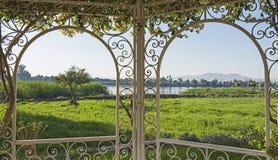 Landelijke plattelandsmening van een rivier in de zomer door latwerk Royalty-vrije Stock Foto's