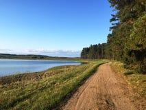 Landelijke weg tussen meer en bos Royalty-vrije Stock Afbeeldingen