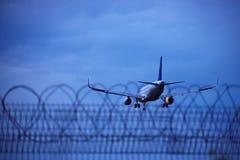 Landend vliegtuig achter de veiligheidsomheining royalty-vrije stock fotografie