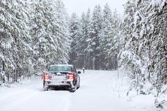 Landfahrzeugfahren auf eine Landstraße im winterlichen Wald Lizenzfreie Stockbilder