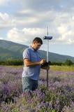 Landfeldmesser, das auf dem Lavendelgebiet arbeitet Lizenzfreie Stockfotos